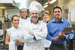26768946 - head chef posing with the team behind him in a profesional kitchen