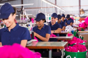 32754657 - group multiracial factory workers sewing in clothing factory