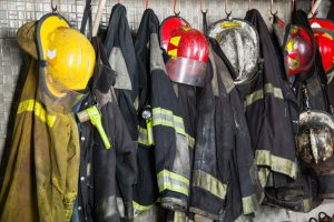 44186423 - firefighter suits and helmets hanging at fire station